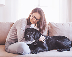 woman hugging dog on the couch